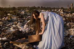 Girl with a suitcase at the dump Royalty Free Stock Photography