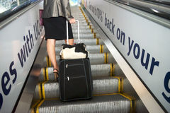 Girl with a suitcase on the escalator Stock Photography