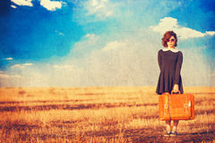 Girl with suitcase on the field Royalty Free Stock Images