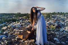 A girl with a suitcase on a garbage dump directed her gaze into the distance Royalty Free Stock Image