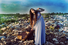 A girl with a suitcase on a garbage dump raised her eyes to the sky Royalty Free Stock Photography