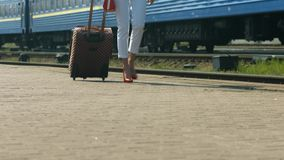 Girl with a suitcase. Girl goes on the platform. Girl traveling stock video footage