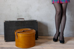 Girl with a suitcase and hat box. In an empty room Royalty Free Stock Photography