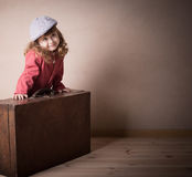 Girl with suitcase indoor Stock Image