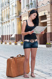 Girl with a suitcase looking at the map. Stock Photography