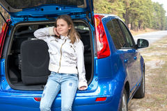 Girl with a suitcase near the car in the woods Stock Images