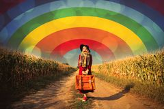 Girl with suitcase near cornfield Stock Photos