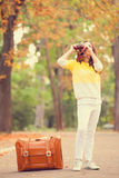Girl with suitcase in the park. Stock Photography
