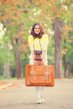Girl with suitcase in the park. Stock Photos
