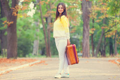 Girl with suitcase in the park. Royalty Free Stock Image