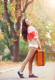 Girl with suitcase in the park. Stock Photo