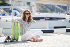Girl with suitcase on the pier near the yacht Royalty Free Stock Photography