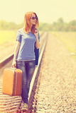 Girl with suitcase at railways. Stock Photo