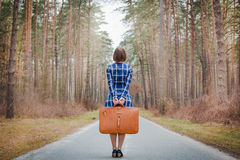 Girl with suitcase on the road Royalty Free Stock Images