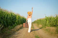 Girl with a suitcase on a rural road in summer Royalty Free Stock Photo