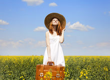 Girl with suitcase at spring rapeseed field. Stock Photos
