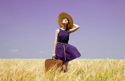 Girl with suitcase at spring wheat field. Stock Photography