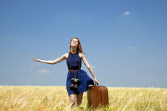 Girl with suitcase at spring wheat field. Royalty Free Stock Images