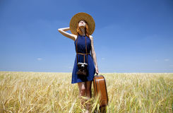 Girl with suitcase at spring wheat field. Royalty Free Stock Photo