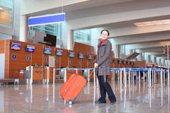 Girl with suitcase standing in airport Royalty Free Stock Photo