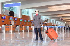 Girl with suitcase standing in airport hall Stock Photo