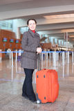 Girl with suitcase standing in airport hall Stock Photos