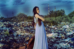 Girl with a suitcase standing on a garbage dump over blue sky background Royalty Free Stock Photo