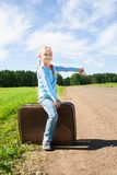 Girl with suitcase standing about road Stock Image