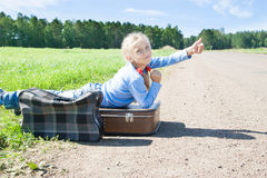 Girl with suitcase standing about road Royalty Free Stock Photography