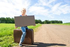 Girl with suitcase standing about road Stock Photos