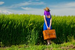 Girl with suitcase standing at wheat field Royalty Free Stock Images