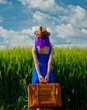 Girl with suitcase standing at wheat field Stock Photo