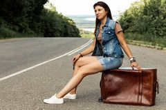Girl with a suitcase stops the car on the road royalty free stock photos