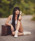 Girl with suitcase stops the car on road. Sexy girl with suitcases, Young sexy woman sitting on suitcases at the roadside Stock Photography