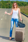 Girl with a suitcase   traveling hitchhike Royalty Free Stock Photos