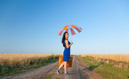 Girl with suitcase and umbrella Stock Photos