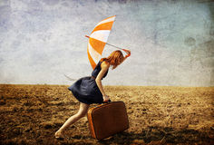 Girl with suitcase and umbrella at field. Royalty Free Stock Photo