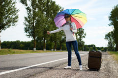 Girl with suitcase and with umbrella near the road Royalty Free Stock Photos