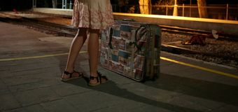 Girl at train station with suitcase during night. Girl with suitcase waiting for her train on the platform in the station during the night Stock Images