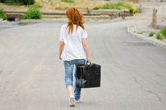 Girl with suitcase walking down the street Royalty Free Stock Images