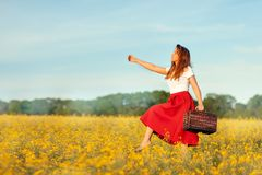Girl with a suitcase walking in the field. Royalty Free Stock Photo