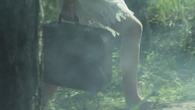 Girl with a suitcase walking on the green grass in wild nature. stock video