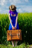 Girl with suitcase at wheat field stock photo