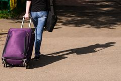 Girl in jeans is on the road with a suitcase royalty free stock image