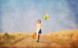 Girl with suitcase and wind toy at countryside Royalty Free Stock Image