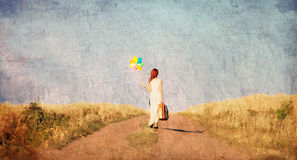 Girl with suitcase and wind toy at countryside Stock Photography