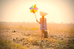 Girl with suitcase and wind toy Royalty Free Stock Photography