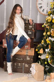 Girl with suitcases in christmas interior. Nice girl with long curly hair at pile of suitcases in christmas interior Royalty Free Stock Photo