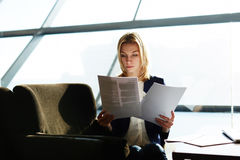Girl in suite waiting departure in airport. Portrait of attractive businesswoman reading papers or documents sitting in luxury coffee shop next to the window stock images