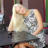 Girl in summer cafe. Beautiful girl with sunglasses sitting at a table in summer cafe Royalty Free Stock Image